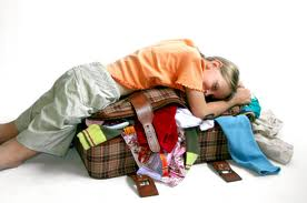 kid laying on suitcase full of clothes