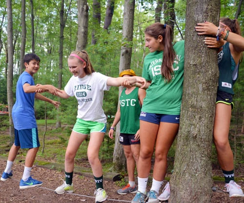 girls doing low ropes course at summer camp