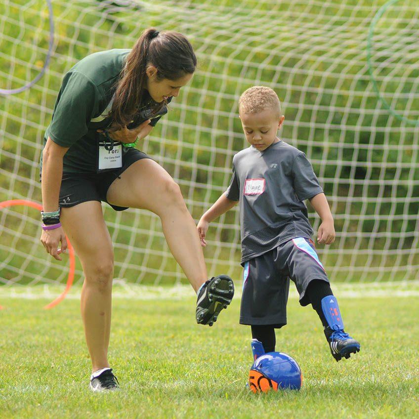 ISTC camp counselor teach boy soccer