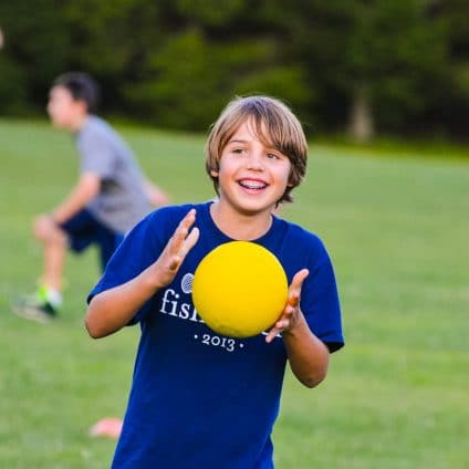 boy holding dodgeball at summer camp