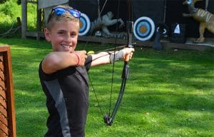 boy doing archery at summer camp