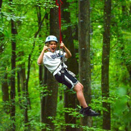 kid swinging through woods