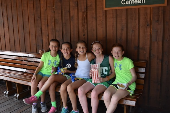 girls at summer camp sitting on bench smiling