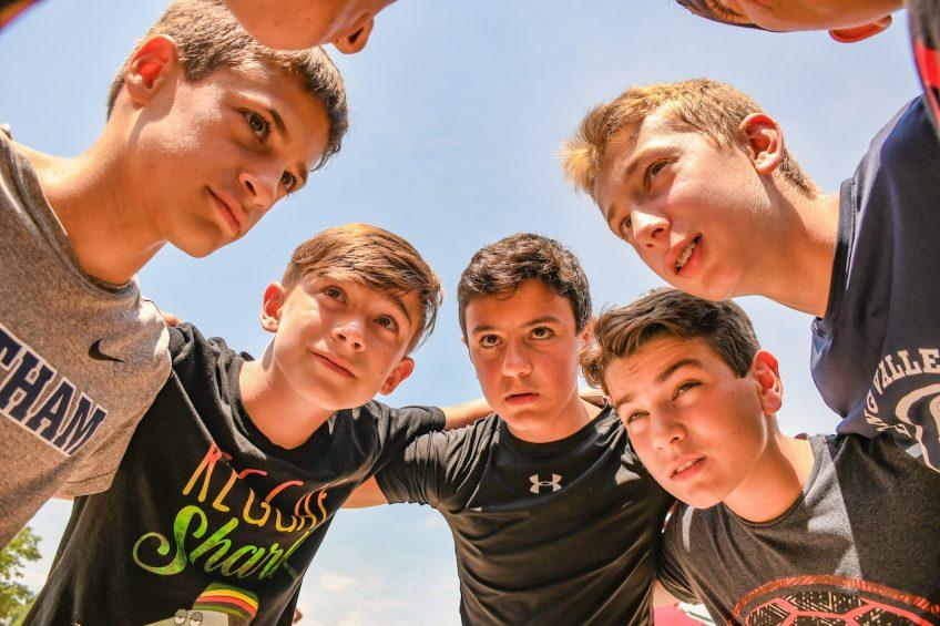 boys huddled in circle at summer camp