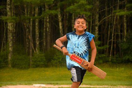 kid running with cricket bat