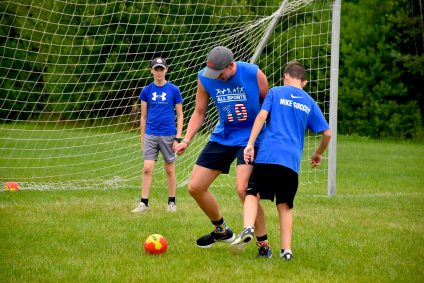 counselor and campers playing soccer