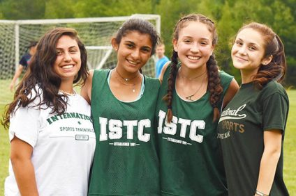 girls at ISTC smiling on soccer field