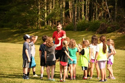 camp counselor giving high fives to campers