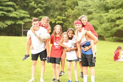 group of kids with camp counselors on field