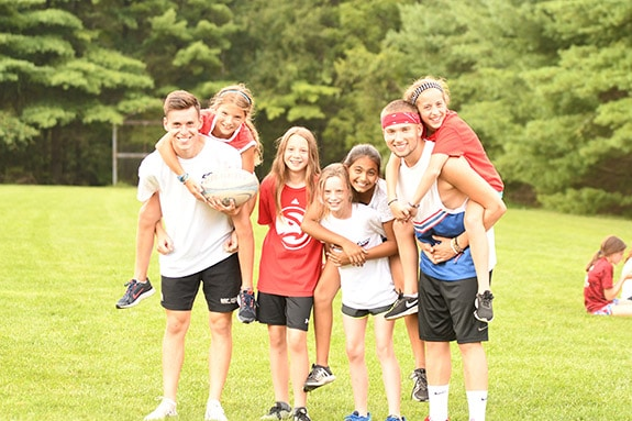 kids with camp counselors on field