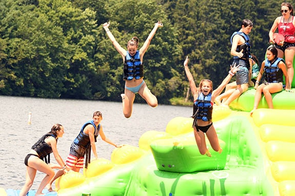 kids jumping on float in water at trout lake