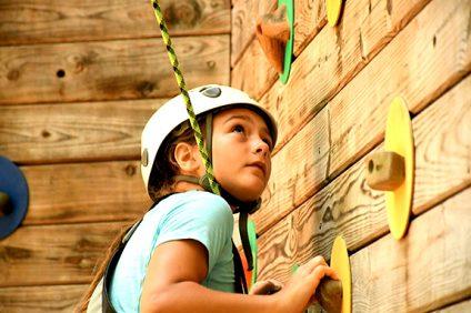 girl on rock wall at summer camp